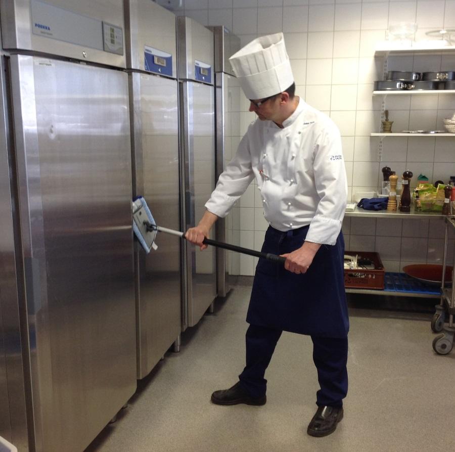Kokki siivoaa keittiössä