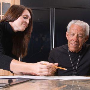 Henkilökohtainen avustaja avustaa työnantajaansa pöydän äärellä