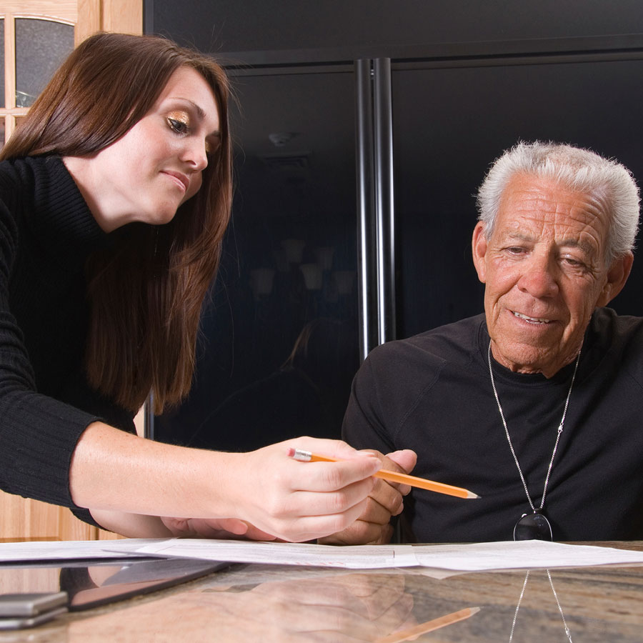Hyvinvointiteknologia-asentaja avustaa vanhempaa henkilöä pöydän äärellä.