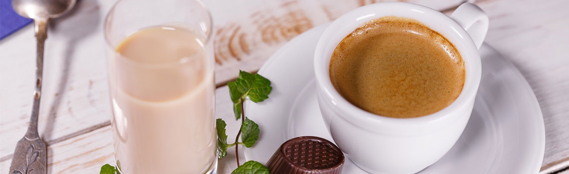 Kahvikuppi. leivos, lusikka ja konvehti pöydällä.