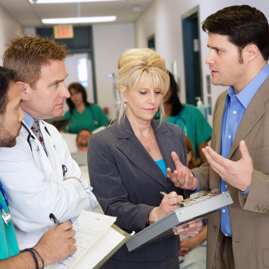 Sote-alan esimiehet keskustelevat sairaalan käytävällä.