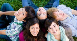 Viisi opiskelijaa istuvat ulkona nurmikolla.