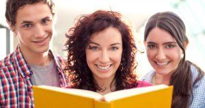 Kolme opiskelijaa kirjan äärellä.