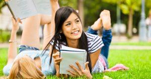 Opiskelijat opiskelevat rennosti nurmikolla.