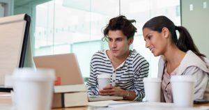 Kaksi opiskelijaa istuvat kannettavan tietokoneen äärellä ja juovat kahvia.