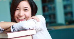 Opiskelija nojaa kirjapinoon ja hymyilee.