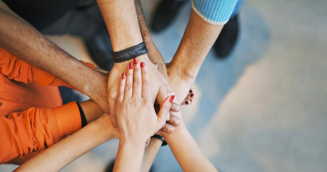 Viiden henkilön kädet yhdessä päällekkäin.