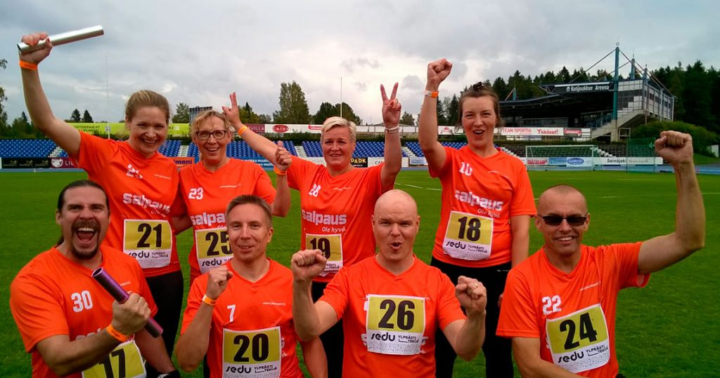 Salpauksen viestijoukueet poseeraavat oransseissa paidoissaan