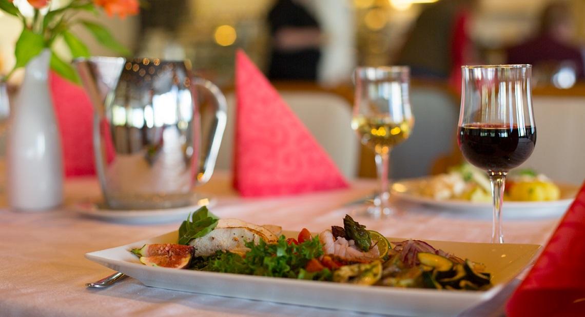 Ruoka-annos ja viinilasit pöydällä.