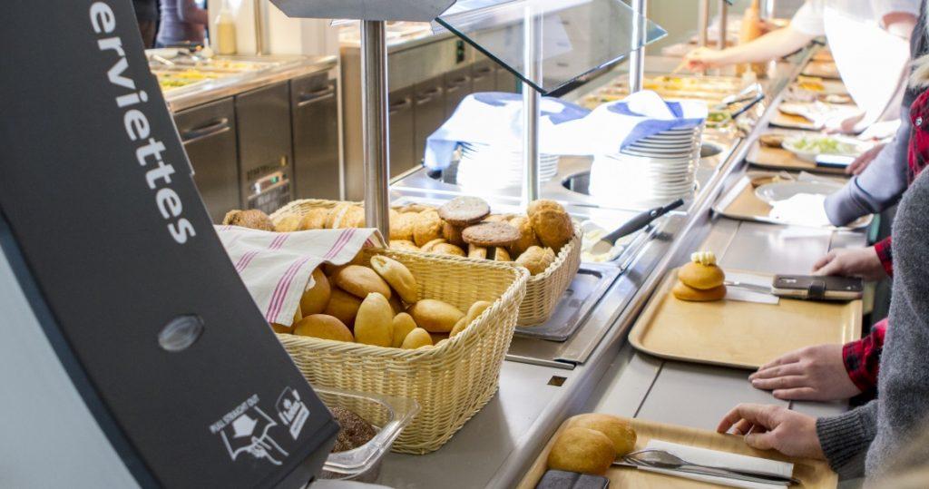 Ruokalinjastolla sämpylöitä etualalla ja ihmisiä ottamassa ruokaa.