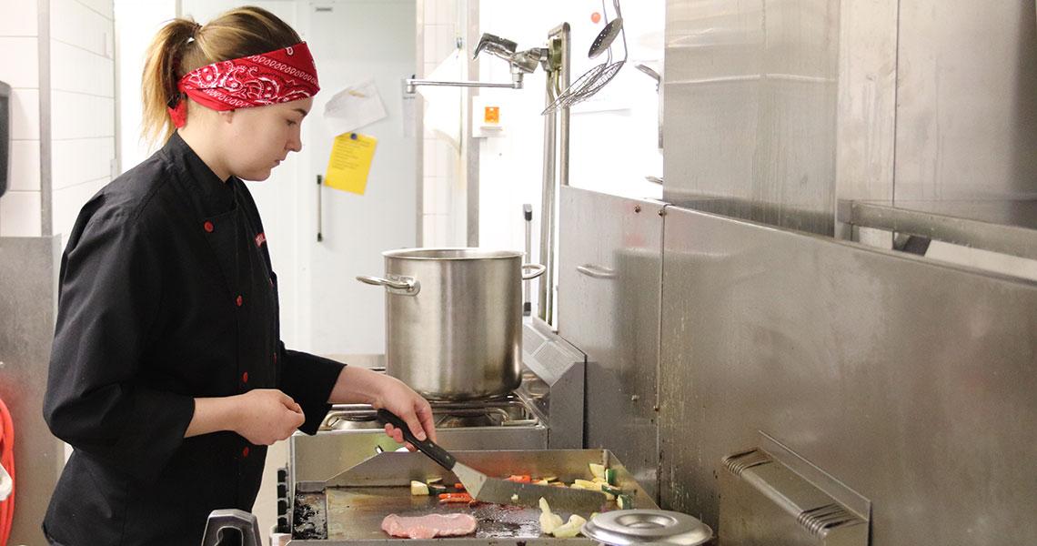 Ella työskentelee Teboil Tähtihovin keittiössä Heinolassa kokkina ja paistaa vihanneksia ja lihaa