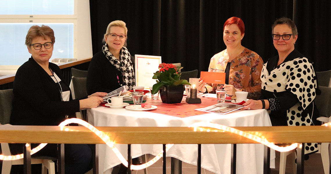 Joululahjoitukseen osallistuneet pöydän ääressä istumassa