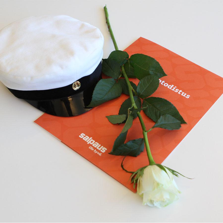 Ylioppilaslakki, valkoinen ruusu ja tutkintotodistus pöydällä.