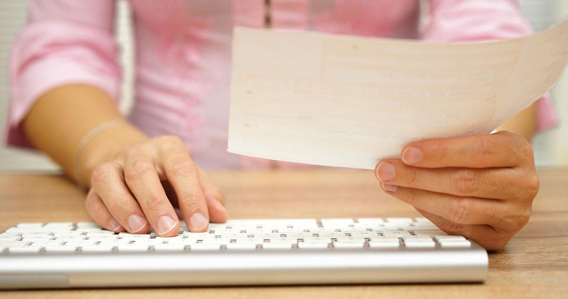 Kädet näppäimistöllä ja toisessa paperi.