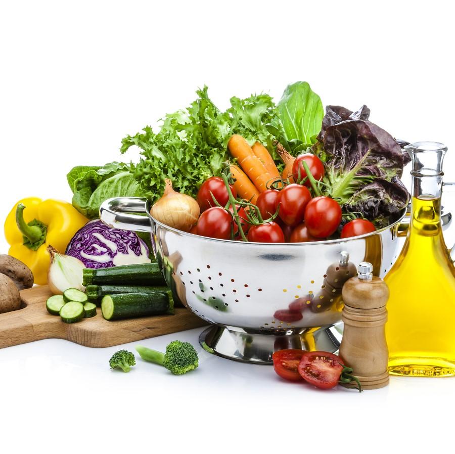 Erilaisia vihanneksia kulhossa ja leikkulaudalla.