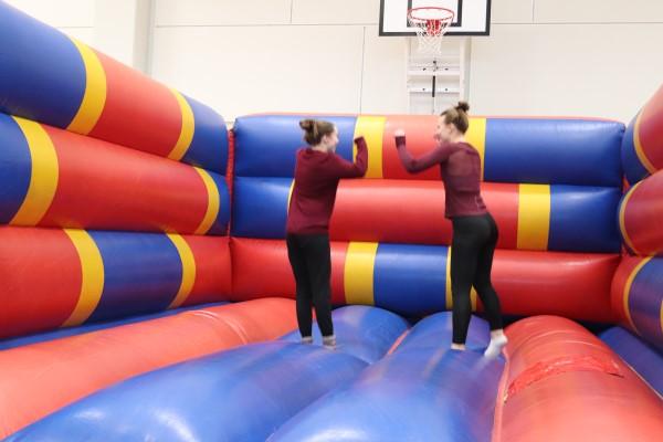 kaksi naista hyppii pomppulinnassa