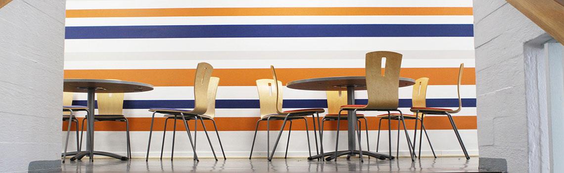 Pyöreitä ruokapöytiä sekä tuoleja värikkään seinän edessä Heinolan kampuksella.