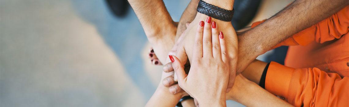 Ihmisten kädet yhdessä toistensa päällä.