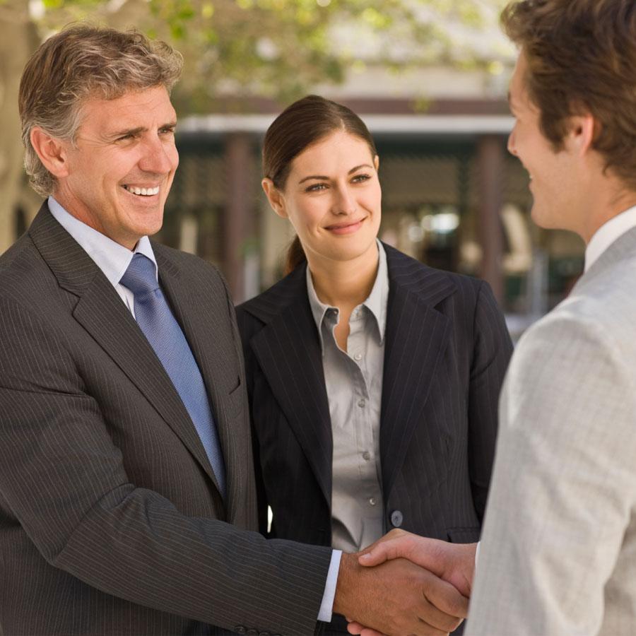 Kaksi miestä kättelee toisiaan hymyillen.