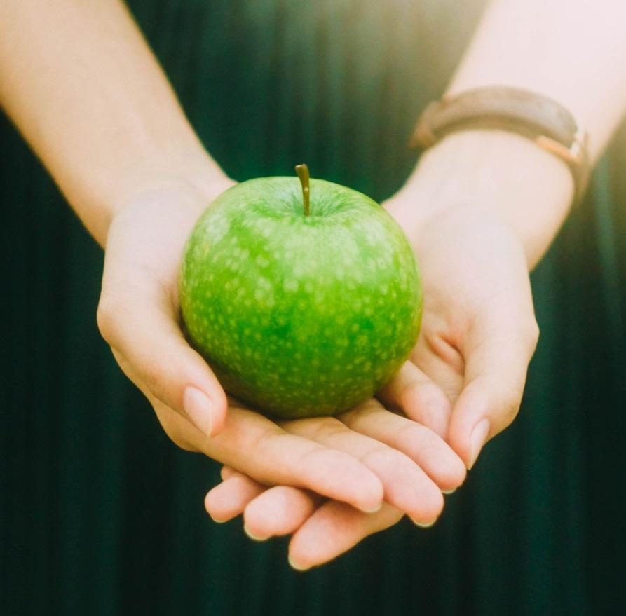 Henkilö pitelee vihreää omenaa käsissään.