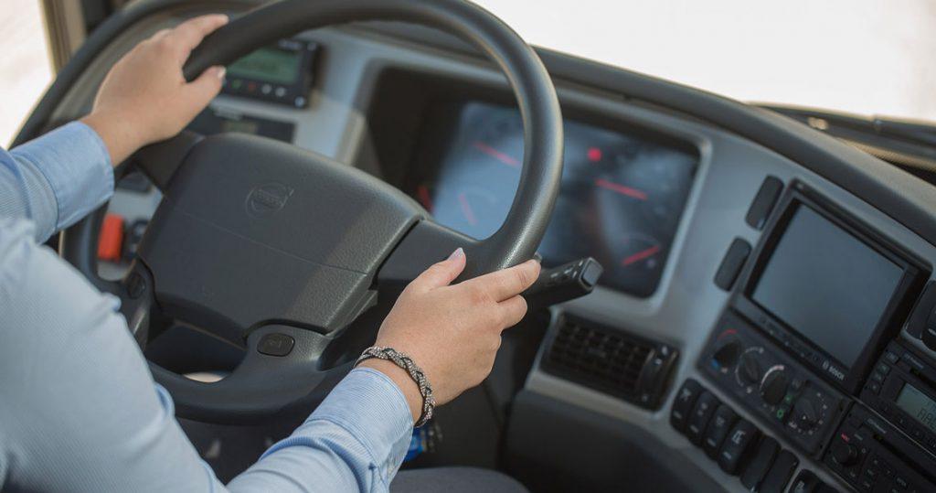 Opiskelija ajaa rekkaa ja pitää käsillään kiinni ratista.