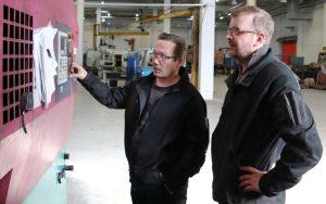 Miehet keskustelevat työpaikalla koneen edessä