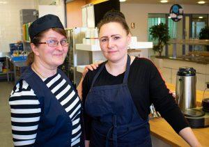 Kaksi iloista naista hymyilee kameralle kahvilinjaston edessä