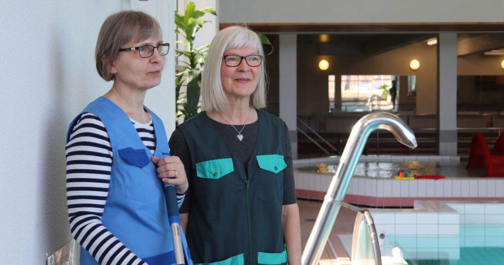Kaksi naista seisoo uimahallissa altaan reunalla ja hymyilevät