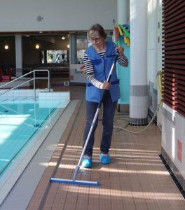 Henkilö siivoaa uimahallissa altaan viereistä laatoitusta