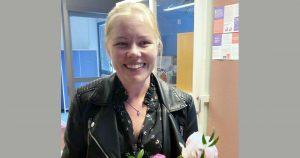 Hymyilevä nainen kukkakimppu kädessään