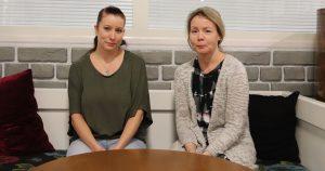 Kaksi naista istuu sohvalla pöydän ääressä