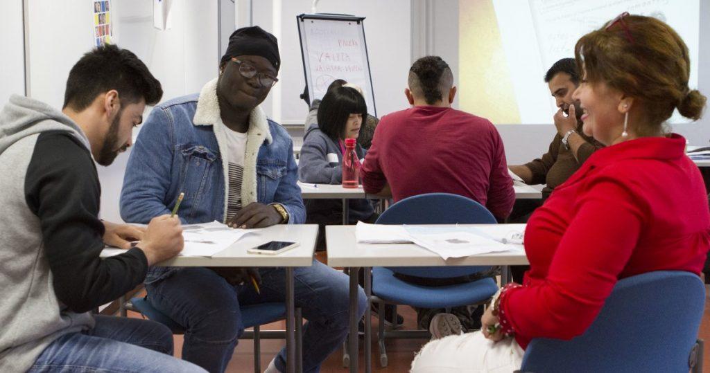 Maahanmuuttajia opiskelemassa työpöydän ääressä