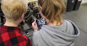 Kaksi opiskelijaa tutkii moottoria ja ottaa kuvaa kännykällä