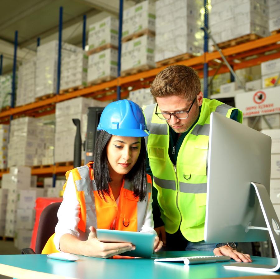 Kaksi henkilöä tehdasympäristössä pöydän ääressä katselevat pädiltä tietoja.