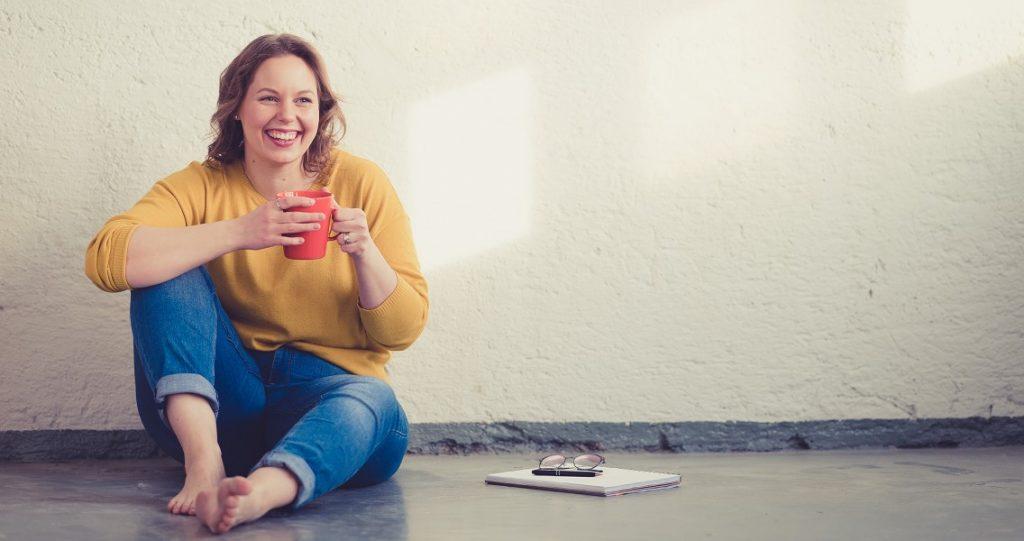 """""""Hymyilevä nainen istuu lattialla kahvikuppi käsissään"""""""