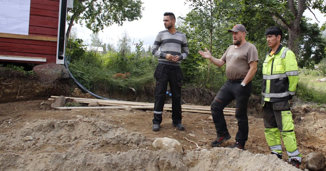 Työnjohtaja esittelee työmaata kahdelle maahanmuuttajataustaiselle rakennusmiehelle.