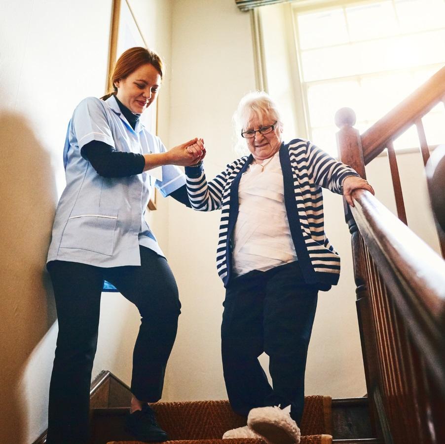 Hoiva-alalla työskentelevä nainen taluttaa vanhempaa naishenkilöä portaissa