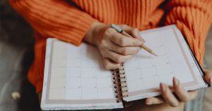 Nainen kirjoittaa kynällä kalenteriin merkintöjä