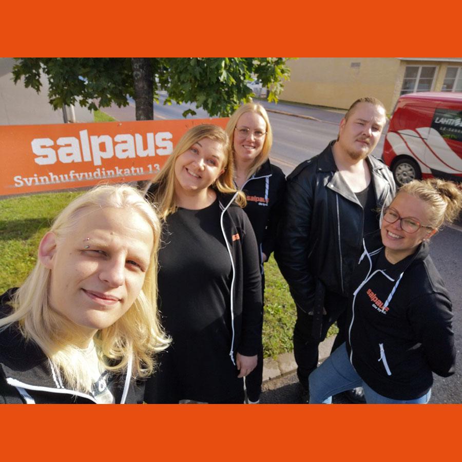 Viiden nuoren ryhmä seisoo ulkona ja hymyilee kohti kameraa.