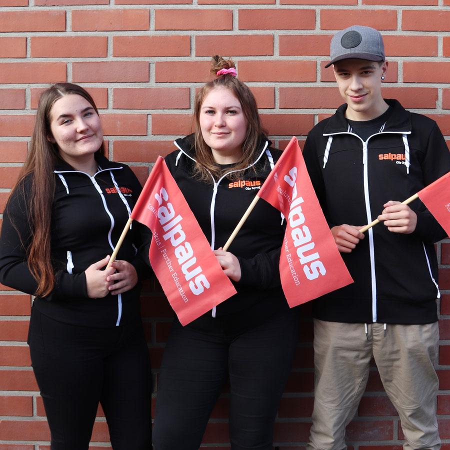 Kolme opiskelijaa Salpaus-liput kädessä ulkona tiiliseinän edessä.