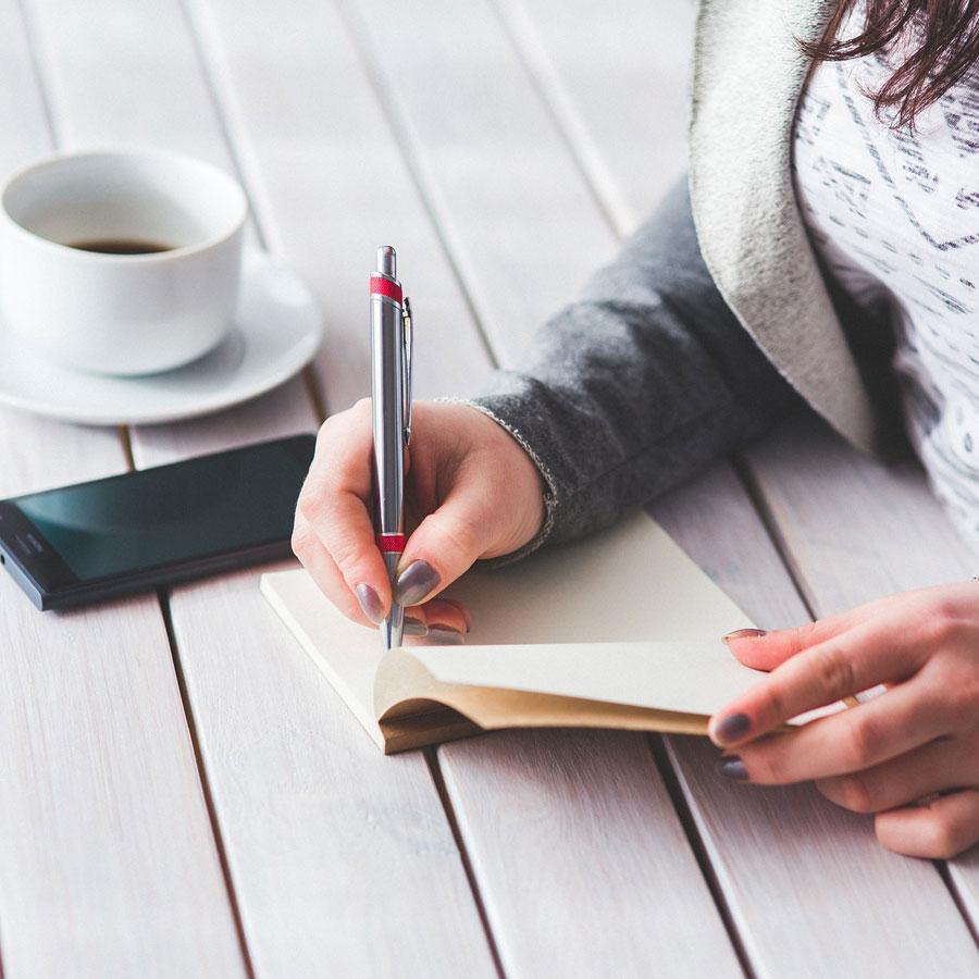 Nainen kirjoittaa muistiinpanoja vihkoon, pöydällä on kahvikuppi ja kännykkä.