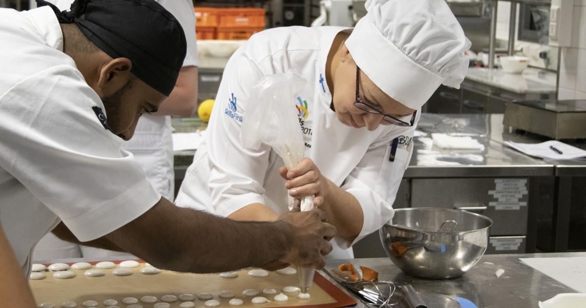 Intialainen ja suomalainen kondiittori pursottavat leipomossa leivoksia.