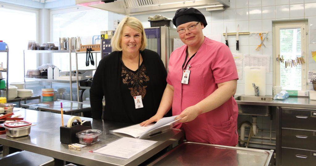 Kaksi naista keittiössä tutkivat kansiota ja sen papereita