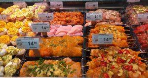 Monenlaisia lihoja, kaloja ja kananmunia kaupan palvelutiskillä.