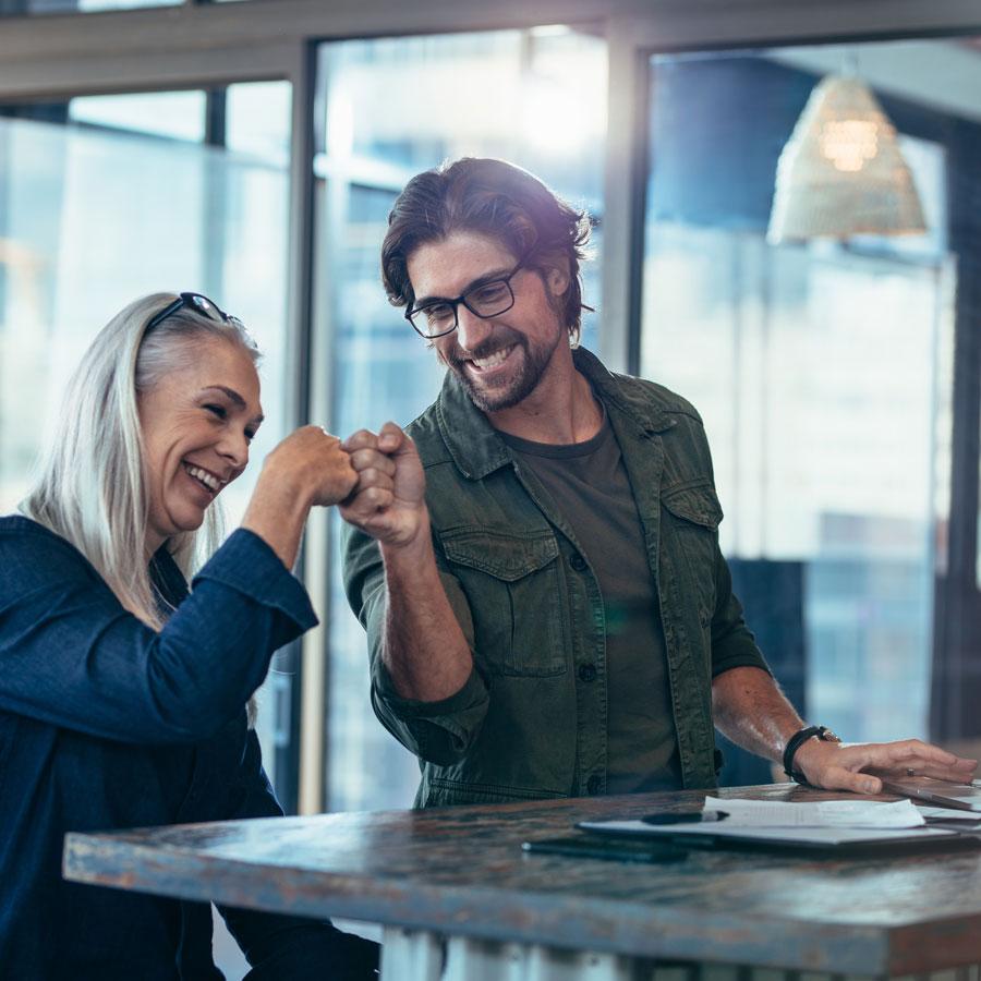Nainen ja mies pistävät nyrkkinsä yhteen voitonmerkiksi ja hymyilevät.