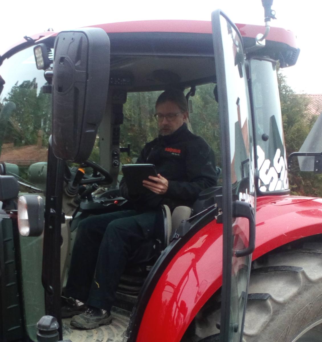mies istuu traktorissa ja selailee tablettia.