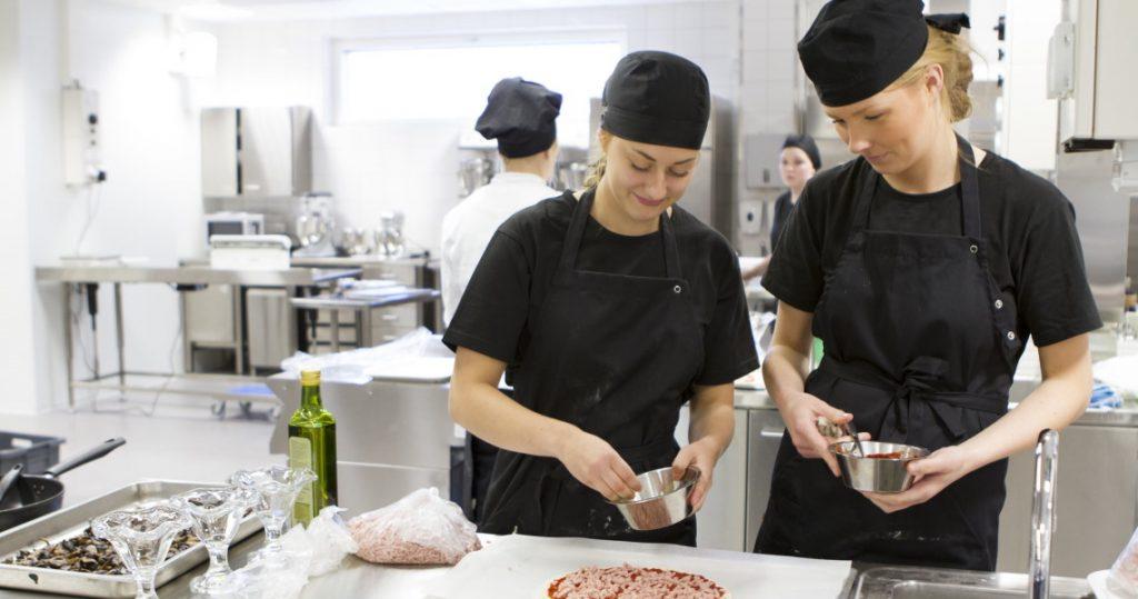 Kaksi kokiksi opiskelevaa nuorta naista täyttävät pitsaa Salpauksen opetuskeittiössä.