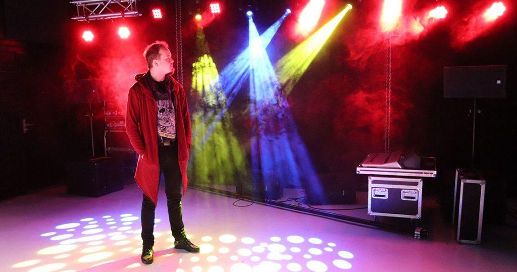 Mies seisoo esityslavalla ja katselee lavan värikkäitä valoja ja savua.