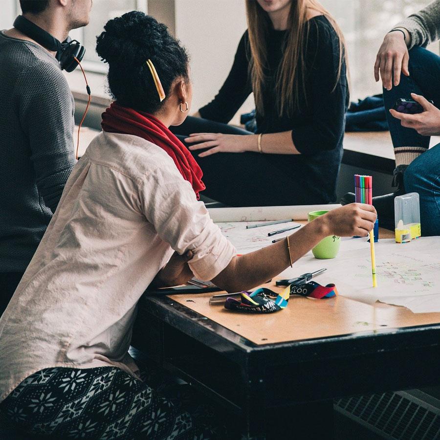 Opiskelijoita pöydän äärellä, pöydällä papereita ja kyniä.
