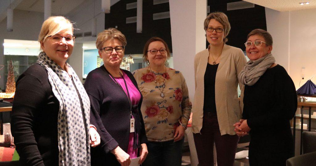 Viisi naista seisoo ryhmäkuvassa